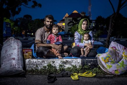 BATAM, INDONESIA - SEPTEMBER 05: An Afghan asylum seeker family, Hasan Remezonei and his wife Farshta with their baby Asma and son Amir, poses at the parking area, nearly three months they was living inside the city park next of regional parliament building city of Batam on September 5, 2016 in Batam, Indonesia. Dozens of asylum seekers from Afghanistan, Sudan, Somalia and Pakistan was forced to sleep in front area of regional parliament building city of Batam at night and live in a city park during the day, as they waiting for registration and resettlement for asylum seekers. In the midst of the global refugee crisis, over 13,500 refugees and asylum seekers are known to have settled in Indonesia as of April 2016, a majority in Jakarta while the remainder in cities like Makassar, Medan and Batam. Although it may be small compared to neighboring countries in the region and 65 million people who had been forced to leave their homes due to war and persecutions in 2015, the numbers of asylum seekers taking Indonesia as their new homes continue to grow as they get trapped in transit while heading towards their destination countries, such as Australia and New Zealand. Refugees, mostly from Afganistan, Sudan and Somalia, are not able to legally work, leave their shelters, formally marry an Indonesian or gain citizenship, creating fatigue within the settlements as Indonesia finds itself hosting a growing number of asylum seekers over increasing periods. (Photo by Ulet Ifansasti/Getty Images)